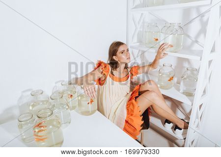 Attractive young woman sitting and relaxing near closet and table with gold fishes in jars