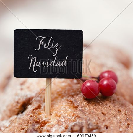 closeup of a black signboard with the text feliz navidad, merry christmas in spanish, topping a christmas cake