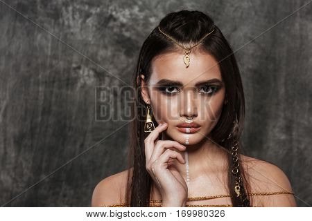 Image of beautiful young asian model with bright makeup and sunburn skin touching face with hand. Looking at camera.