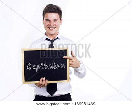 Capitalism - Young Smiling Businessman Holding Chalkboard With Text