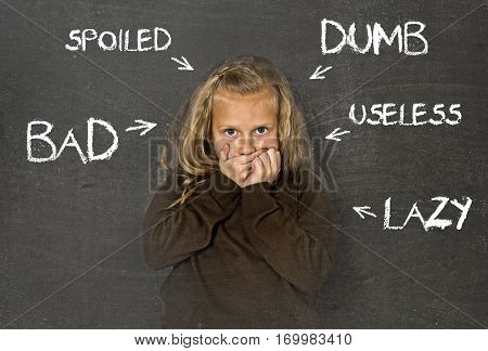 little beautiful blond schoolgirl sad ashamed and embarrassed being pointed and marked on school class blackboard with words lazy useless bad spoiled and dumb in abuse discipline concept