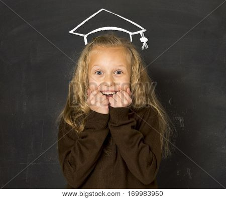 young beautiful blond sweet schoolgirl in uniform laughing excited in front of school class blackboard smiling happy with chalk sketch drawing of graduation hat smiling happy in education future success