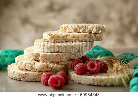 Round rice crispbreads with raspberries and measuring tape, closeup