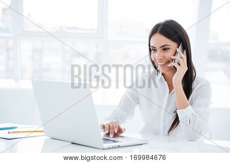 Side view of Business woman talking at phone and sitting by the table with laptop in office