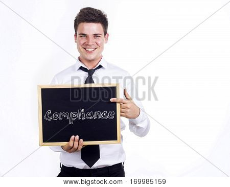Compliance - Young Smiling Businessman Holding Chalkboard With Text