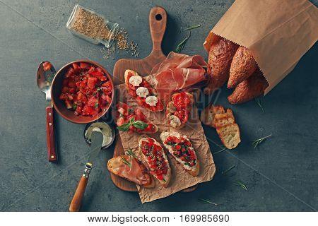 Tasty bruschettas on cutting board on black background, top view