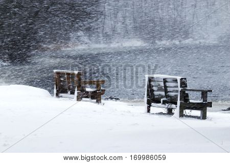 Snow blowing sideways at Southards Pond NY with two benches in the picture