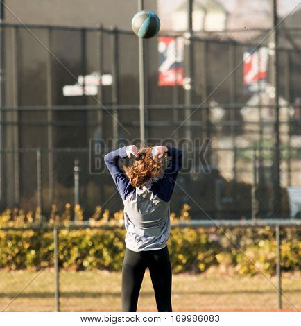 Female high school track and field athlete throwing a medicine ball backwords