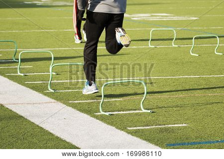 A runner sprints over small green hurdles on a green turf field in the winter