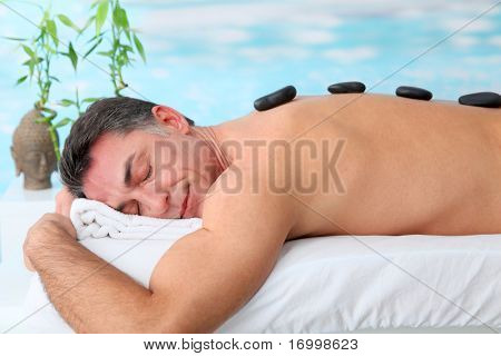 Man laying on massage bed with hot stones poster