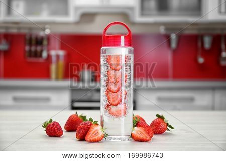 Bottle with strawberry-infused water on kitchen table