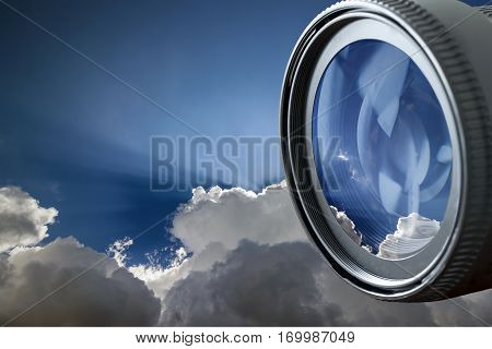 Blue sky with puffy white clouds in bright clear sunny day in digital photo camera lens reflection. Professional Photography Equipment Photographer Work Kit.