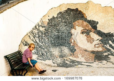 Lisbon, Portugal - Septmember 19, 2016: Old woman sitting by a portrait of fado singer Amalia Rodrigues by artist Vhils