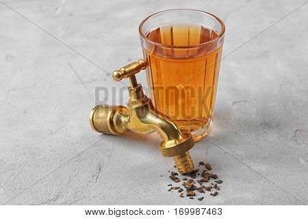 Water shortage concept. Glass of dirty water and tap on light background