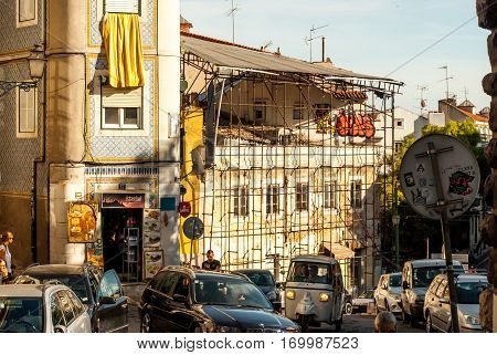 Lisbon, Portugal - Septmember 19, 2016: Old facde with plaster coming off showing brickstone, an apparently closed shop, ancient looking scaffolding and an open kebab shop, traffic in front of it