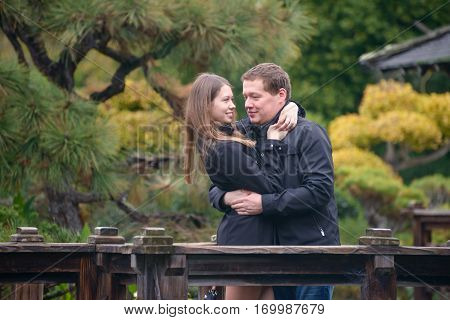 Young romantic couple - good-looking man and attractive woman with long hair - standing on the bridge in beautiful Japanese garden, talking and hugging.