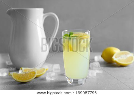 Glass of refreshing lemonade on table