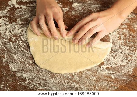 Female hands and rolled out dough on kitchen table, close up