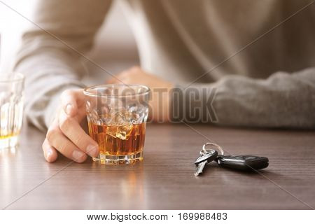 Drunk man with car key and alcoholic beverage in bar, closeup. Don't drink and drive concept