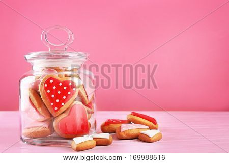 Valentine's day cookies in glass jar on pink background