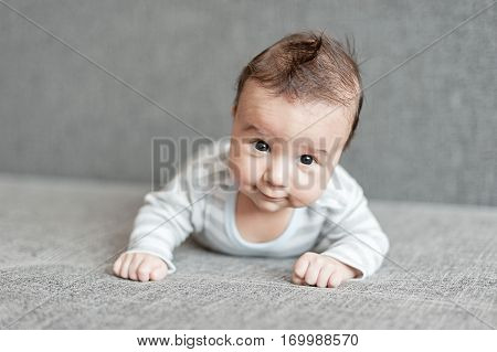 Newborn child relaxing in bed. Nursery for young children. Cute baby boy lying on his tummy