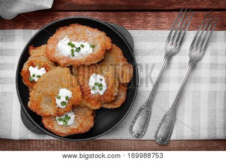 Pan with tasty potato pancakes for Hanukkah on wooden table