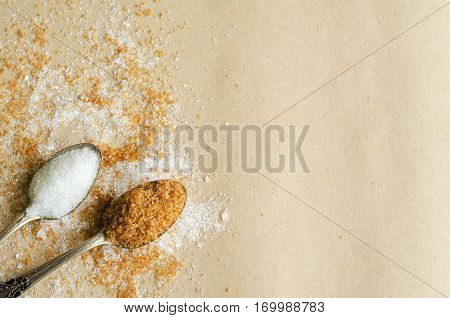 Two tea spoons of cane and white sugar on craft packaging parchment paper background