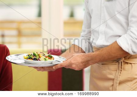 Close up view of waiter serving salad at restaurant