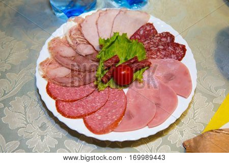 Plate of cold sliced meat on the table. Table ham and bacon - the view from the top. Festive food and refreshments served. Gluttony and gluttony is human. Consumption of food in large quantity.