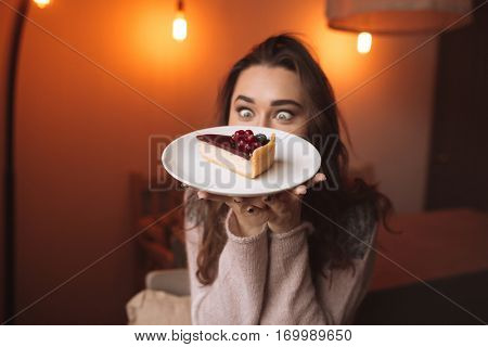 Photo of hungry young lady with long hair sitting at the table in cafe and looking at cake. Focus on cake.