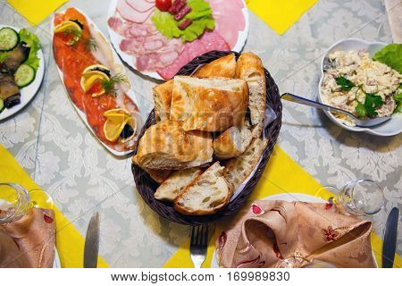 Table with abundant food - top view. Festive food is served. Gluttony is human consumption of foods in large quantity.