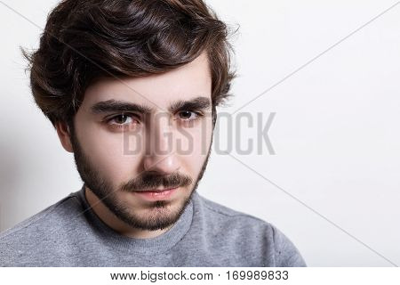 Portrait of sullen angry man with trendy hairstyle and dark beard wearing grey casual sweater looking at camera with serious and severe face expression demonstrating his masculanity.