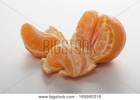 Smal easy peeler orange partially peeled and split into pieces