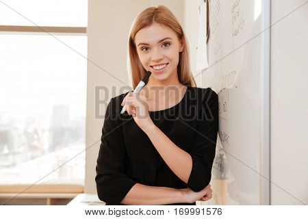 Picture of businesswoman writing on flipchart while giving presentation to colleagues standing in office. Looking at camera.