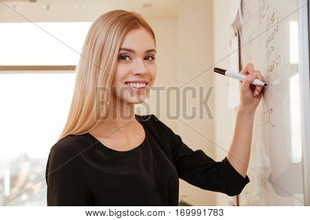 Businesswoman writing on flipchart while giving presentation to colleagues in office. Looking at camera.