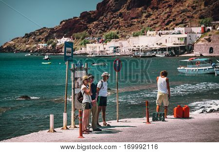 Akrotiri, Santorini, Greece - August 2015: People are staying at a bus stop and waiting for a bus near Akrotiri town on Santorini island.
