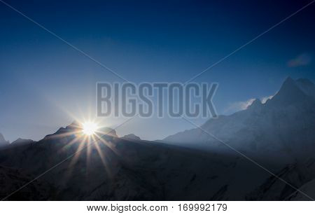 Before sunrise from Annapurna Base Camp (ABC) Trekking on the trail in the mountains. Sport girl with backpack travels in Himalayas. Nepal trek to ABC. Female traveler near Annapurna Base Camp. Snow a
