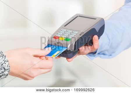 Paying with credit or debit card in wireless payment terminal at shop