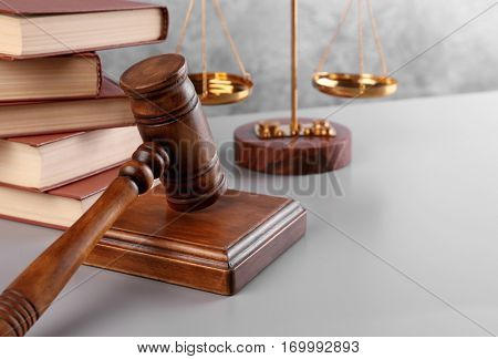 Judge's gavel with books and scales on wall background