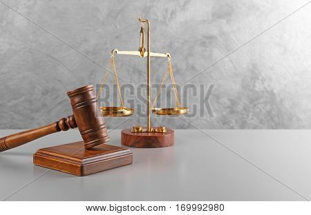 Judge's gavel and scales on wall background
