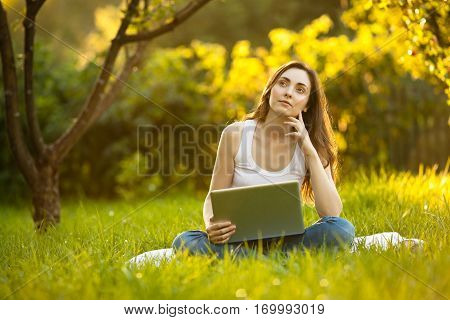 Woman working on laptop stiiting on the green grass and thinking