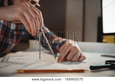 Close up portrait of a man hands using compass to draw a graph while sitting in the office