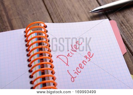 Notepad with text, close up. Driver license concept