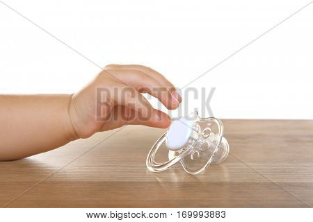 Child hand with pacifier on wooden table