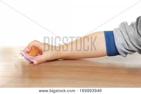 Child hand holding pacifier on wooden table