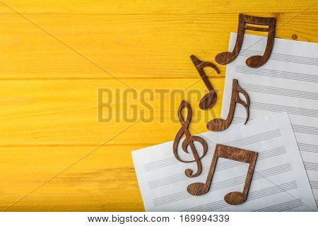 Musical notes lying on music sheets on yellow wooden background
