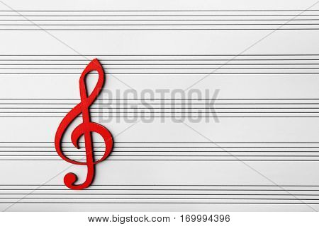 Red wooden musical clef on music sheet background