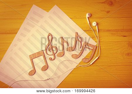 Musical notes and earphones lying on music sheet on yellow wooden background