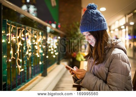 Young woman sending sms on mobile phone at night