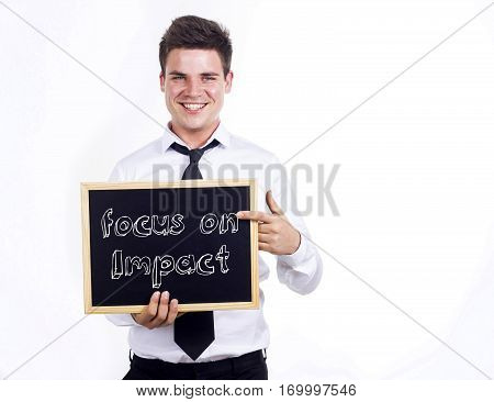 Focus On Impact - Young Smiling Businessman Holding Chalkboard With Text